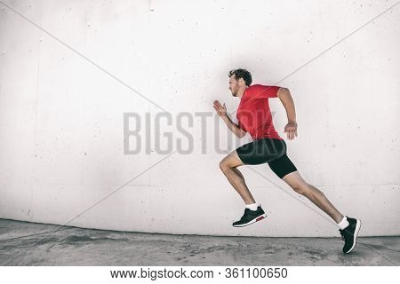 Running man fit athlete male runner working out outside doing city street run sprinting along gym wall. Sprinter going fast living active lifestyle doing sprint hiit high intensity interval training.