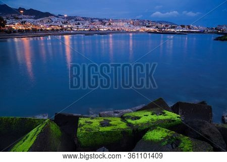 Beautiful night scene over Costa Adeje with colorful lights reflected in the sea in Tenerife, Canary island, Spain.
