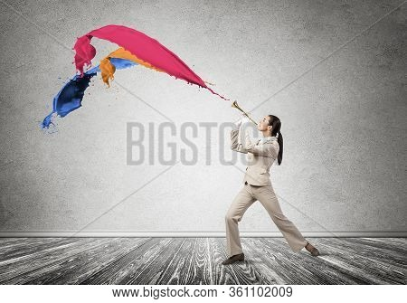 Woman Playing Trumpet Brass Instrument. Colorful Paint Splashing Out From Trumpet. Young Businesswom