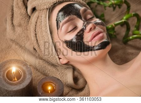 Beautiful woman with purifying black mask on her face. Beauty model girl with black facial peel-off mask lying in spa salon. Skin care, acne treatment, cleansing   skin. Peel of charcoal mask