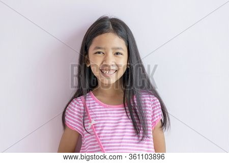 Asian Little Girl Smiling Brightly. Children Wearing Pink Cross White Dresses And Long Black Hair. T