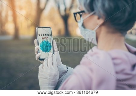 Senior woman with Covid-19 app looking at her phone