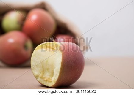 Bag With Apples. Red Apples In A Burlap Bag On A Wooden Background. Fabric Bag Full Of Apples.