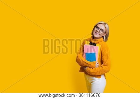 Blonde Student With Eyeglasses Smiling At Camera And Holding Some Books While Posing On A Yellow Wal