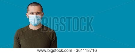 Stressed Caucasian Man Wearing A Medical Mask Is Posing On A Blue Background With Freespace