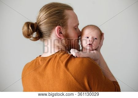 Closeup Portrait Of Young Bearded Caucasian Father Hugging And Kissing Newborn Baby. Male Man Parent