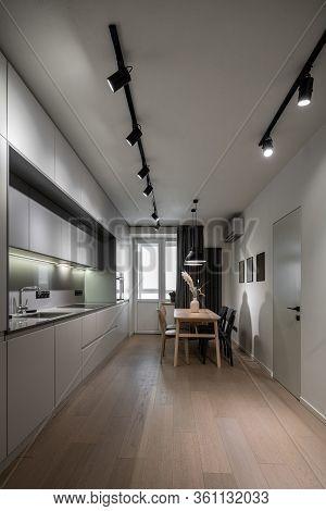 Interior Of Illuminated Modern Kitchen With White Walls