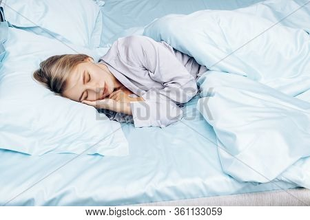 Beautiful Girl Alone Sleeps In Bed. A Young Woman Lies On Blue Silk Bedding On A Hotel Bed. Blue Bed