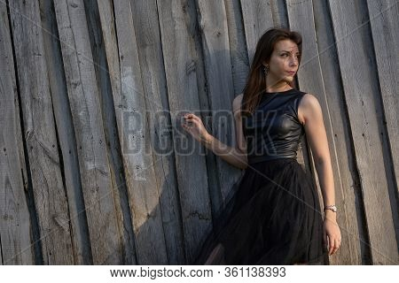 Portrait Of A Young Slim Woman Brunette In A Black Dress Near A Wooden Fence. Summer Sunny Evening.