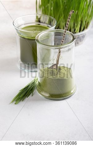 Wheatgrass Shot. Organic Green Drink, Wheatgrass Powder And Wheat Sprouts  On White. Green Superfood