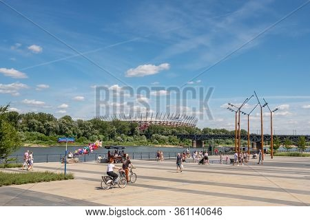Warsaw, Poland - June 29, 2019: Beautiful Vistula riverfront with people walking and riding bicycles at sunny summer day in Warsaw. National stadium at background