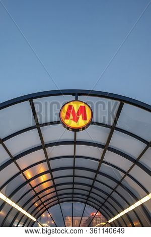 Warsaw, Poland - June 5, 2019: Warsaw metro sign at entrance to underground at night. Company signboard Warsaw Metro