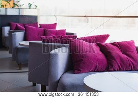 Empty Cushions And Sofas At A Generic Cafe. Clean Table And Chairs Against The Bright Light, Generic