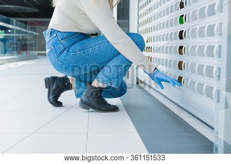 Woman In Hand Gloves Closes The Roller Blinds Of A Store At A Shopping Mall. Lock Down, Close Down O