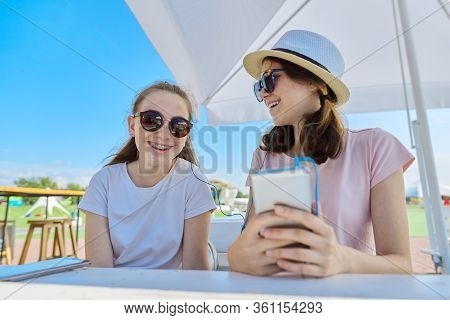 Two Teenage Girls In Headphones Listening Music On Smartphone, Having Fun On Sunny Summer Day. Youth