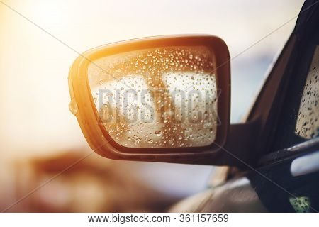 The Rearview Mirror On A Passenger Car Is Wet From Raindrops And Is Illuminated By Sunlight.