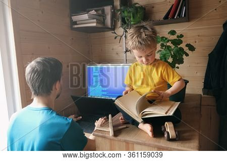 Father Developer Freelancer Work From Home, Child Sits Near And Leafing Through Book, Concept Of Sel