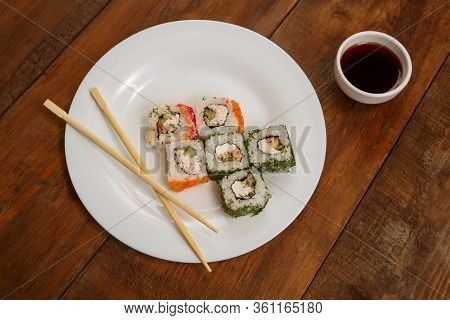 Assorted Rolls With Salmon And Masago Caviar On A White Plate Soy Sauce.