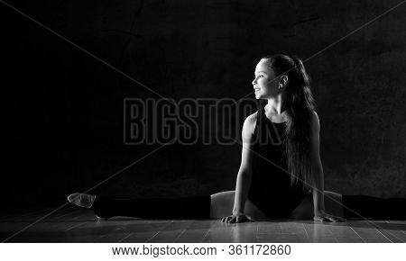 Young Smiling Girl Gymnast In Black Sport Body And Uppers Sitting In Twine On Floor And Holding Pink