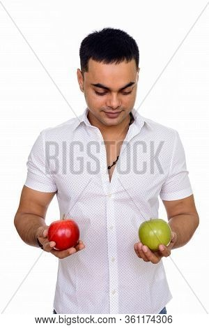 Studio Shot Of Young Handsome Indian Man Holding Red And Green Apple Isolated Against White Backgrou