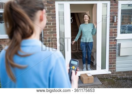 Female Delivery Driver Leaving Package Outside House For Safety Observing Social Distancing During C