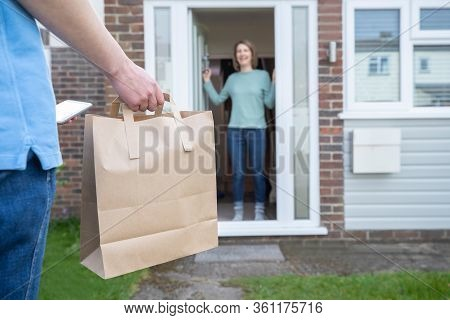 Home Delivery Of Takeaway Food Outside House Observing Safe Social Distancing During Coronavirus Cov