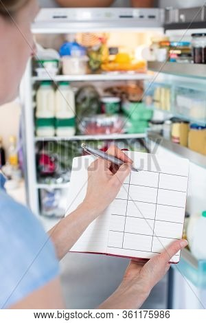 Woman Standing In Front Of Refrigerator In Kitchen With Notebook Writing Weekly Meal Plan