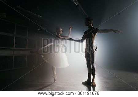 Professional Ballet Couple Dancing In Spotlights Smoke On Big Stage. Beautiful Young Woman And Man O