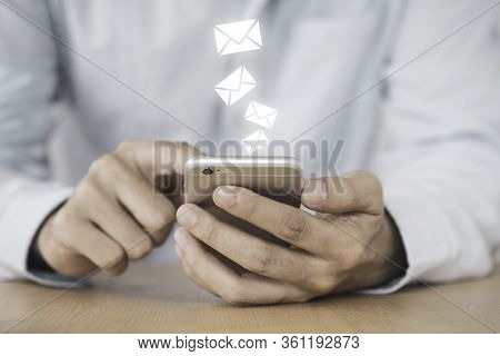Businessman Touching On Mobile Phone Monitor To Send Electronic Mail (e-mail). Work From Home Or Eve