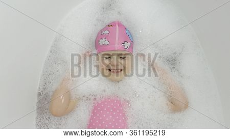 Attractive Four Years Old Girl Takes A Bath With Bath Foam In Pink Swimwear And Swimming Cap. Lying