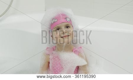 Attractive Four Years Old Girl Takes A Bath With Bath Foam In Pink Swimwear And Swimming Cap. Bath F