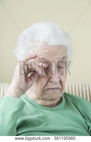 A Senior Woman Itching Her Eye And Face