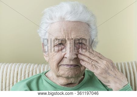 Old Woman Touching Her Face, Risky For Covid-19 Contamination
