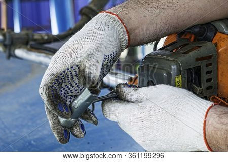 The Master In Working Gloves Repairs The Engine Of The Old Gas Trimmer And Unscrews The Carburetor A
