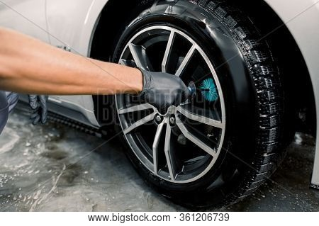 Auto Wash Service. Cropped Close Up Image Of Male Hands In Black Protective Gloves, Cleaning Alloy W