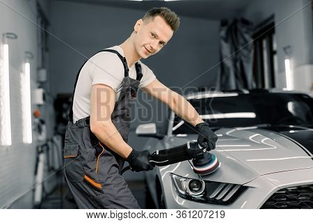 Young Handsome Smiling Caucasian Man, Worker Of Auto Detailing Service, Holds A Polisher In The Hand