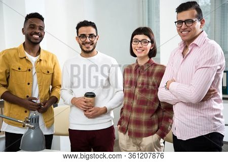 Team of multy-ethnic group of business people standing at the office and smiling at camera