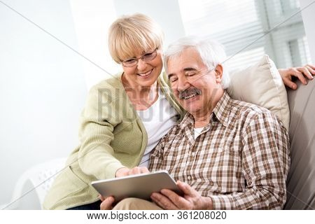 Happy elderly couple have fun at home with a tablet computer