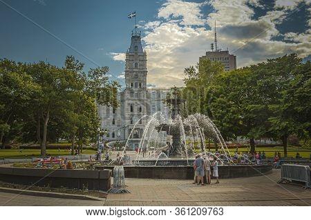Quebec City, Quebec, July 2012 - Tourists Flocking Round The Fountain De Tourny Facing The Parliamen