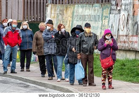 Ruzomberok, Slovakia - April 14: People In Face Masks Waiting In Wor Due Social Restrictions Against