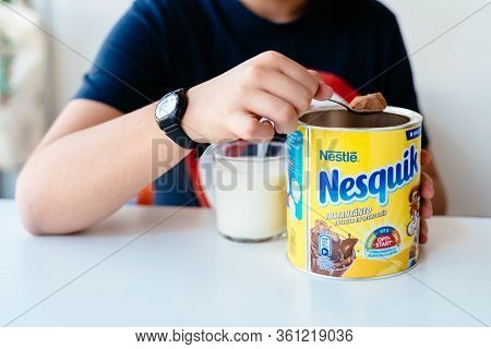Madrid, Spain - April 1, 2020: Boy Serving Nesquik Cocoa Powder In A Glass Of Milk. Nesquiq Is A Tra
