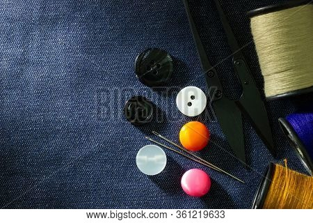 Needle And Threads Against Plastic Button And Thread Cutting Scissors On Jeans Fabric. Top View And