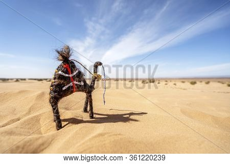 Small Camel Toy Standing On Sands Of Sahara Desert, Africa