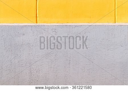 Yellow Concrete Wall And Grey Plinth As Texture Or Background. The Geometric Style. The Plastered Su