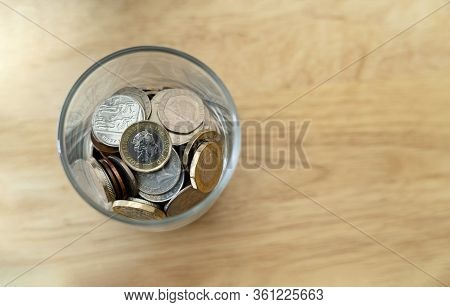 New One Pound British Sterling Coin And Penny And In Glass Bottle On Wooden Table, Concept Financial
