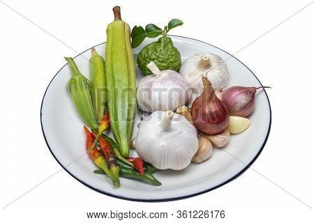 Thai Spice  Fragrant Garlic, Chilies, Kaffir Lime Balls, Okra In A White Background Dish
