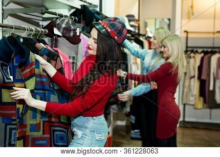 Three Joyful Young Women Shopping Warm Jackets At The Apparel Store. Shopping, Fashion, Clothes, Sty