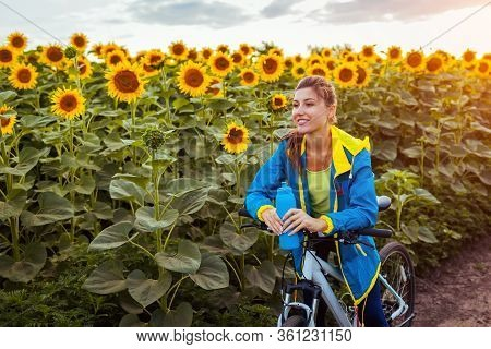 Happy Woman Bicyclist Riding Bicycle In Sunflower Field Holding Water Bottle. Summer Sport Activity.