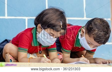 Kids Busy In Writing With Medical Face Mask Wearing Due To Covid-19 Or Coronavirus Outbreak Or Pande