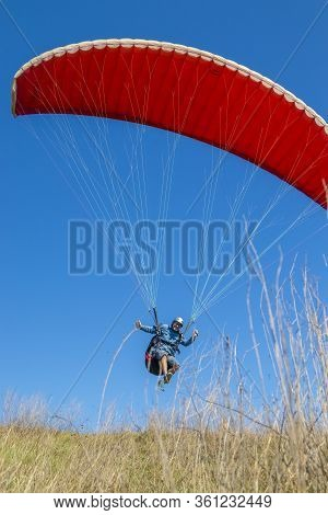 Kyiv Oblast / Ukraine - April 12, 2020: Cheerfully Grinning Excited Paraglider Pilot Is Taking Off U